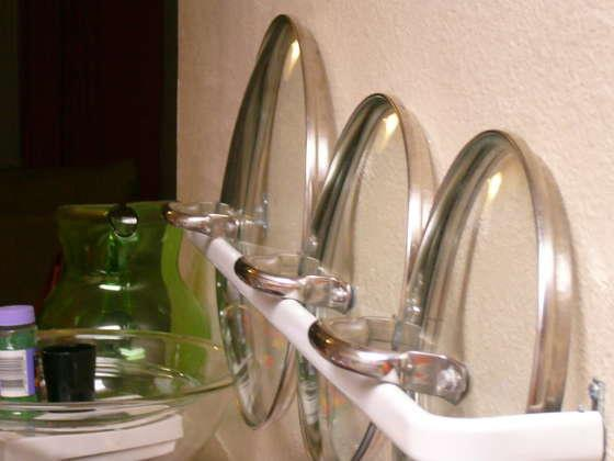 Use a towel rack to hold pot lids
